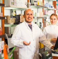 a male pharmacist smiling with a woman behind