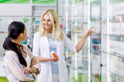 smiling pharmacist holding containers with medication and consulting customer in a drugstore